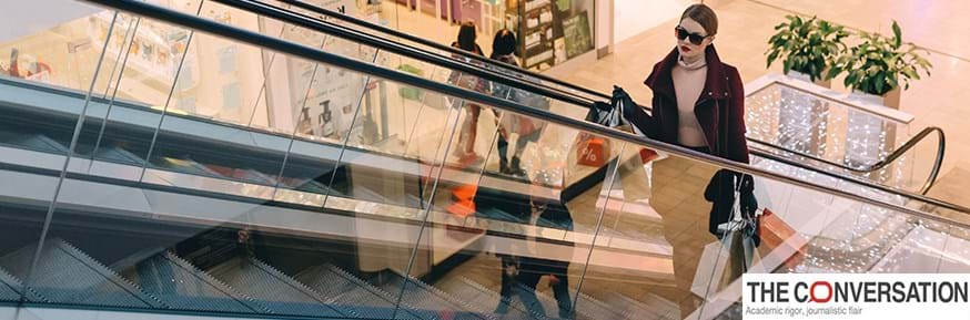A woman carrying lots of shopping bags on an escalator inside a shopping centre