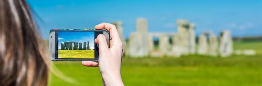 A woman takes a photo of Stonehenge on her phone.