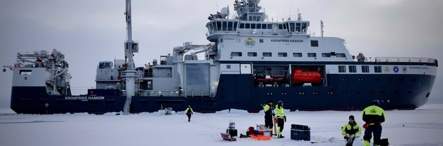 And arctic icebreaker ship - white decks and blue hull - with orange lifeboat and a variety of cranes and high tech equipment. In the foreground scientists in black and yellow high-visibility wear are on the ice taking samples with a variety on equipment