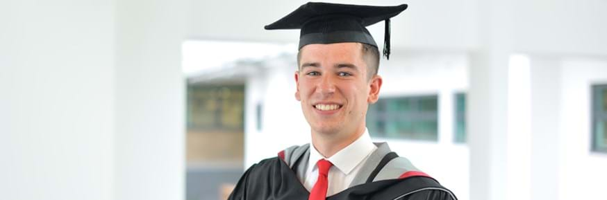 Ben Teague smiling in Lancaster Environment Centre wearing his black, red and grey graduation gowns
