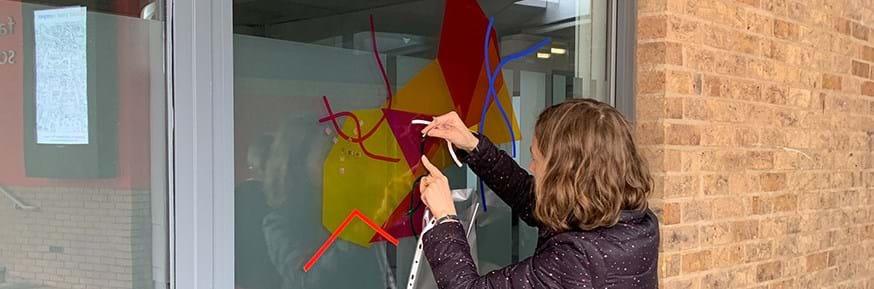 Pattern artist Bonnie Craig tests materials (translucent vinyl) on campus windows.