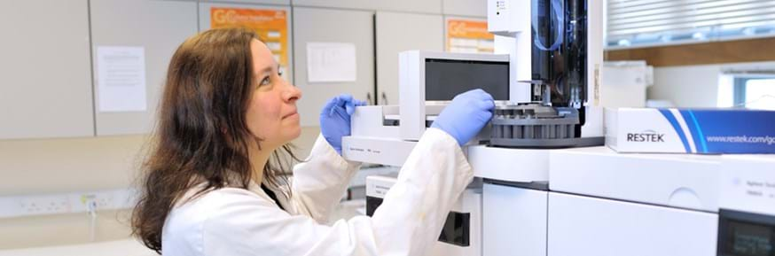Wearing a white lab coat and blue lab gloves, Carola looks up at a large analytical machine while loading small glass vials into it