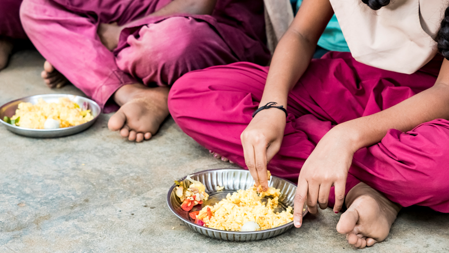 Indian children eating food from tin plate
