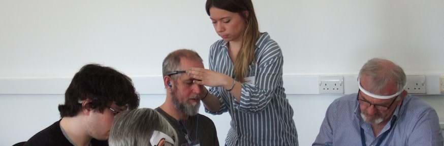 A researcher helps a participant with a head mounted wearable technology