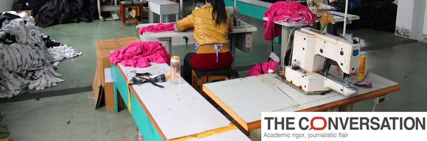 A woman working at a sewing machine in a clothing factory