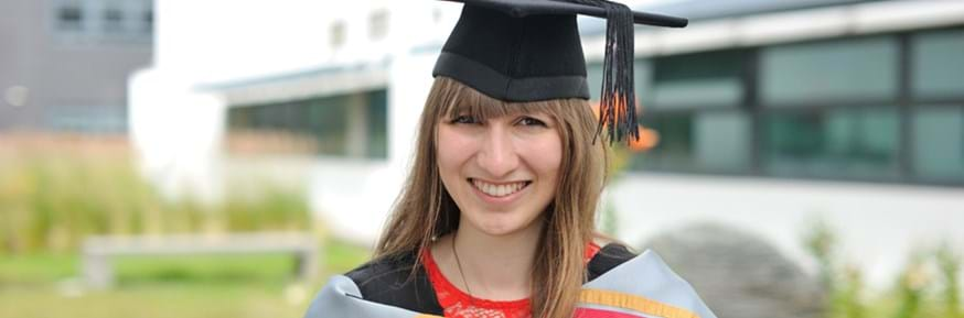 Smiling Eleanor Tinsley in graduation gown and mortarboard hat in one of the Lancaster Environment Centre garden areas