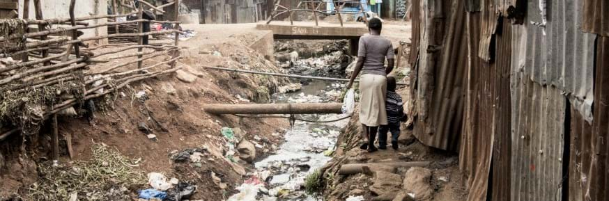 People walking by an open sewer in Africa