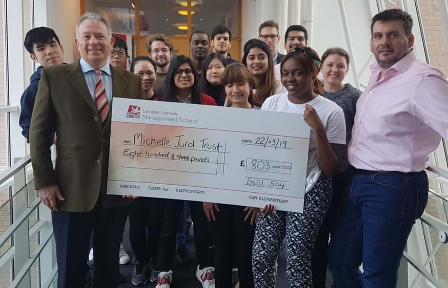 Neil Jurd (front left) accepts a cheque for £803 for the Michelle Jurd Trust from students on the Entrepreneurship in Practice post-graduate module and LUMS Teaching Fellow Brian Gregory (right)