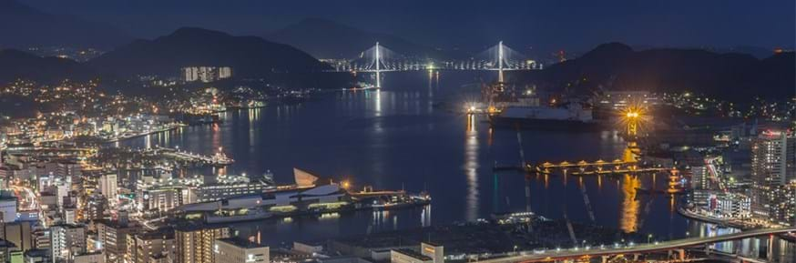 The lights of the city and harbour of Nagasaki, Japan shining at night, in front of the two-pillar suspension bridge