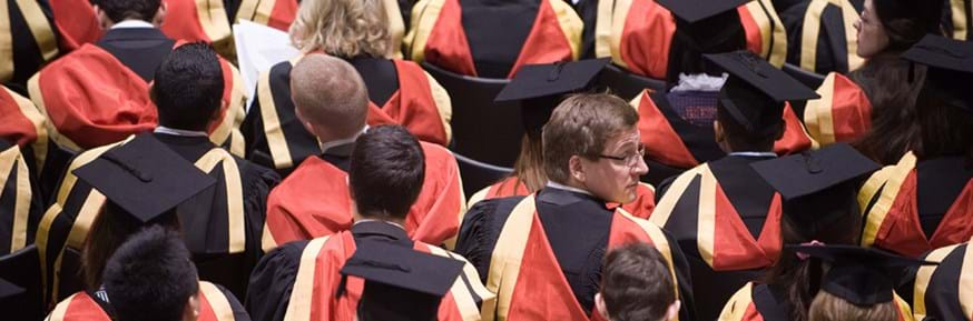 Graduating postgraduate students in black gowns, red and gold hoods and black hats