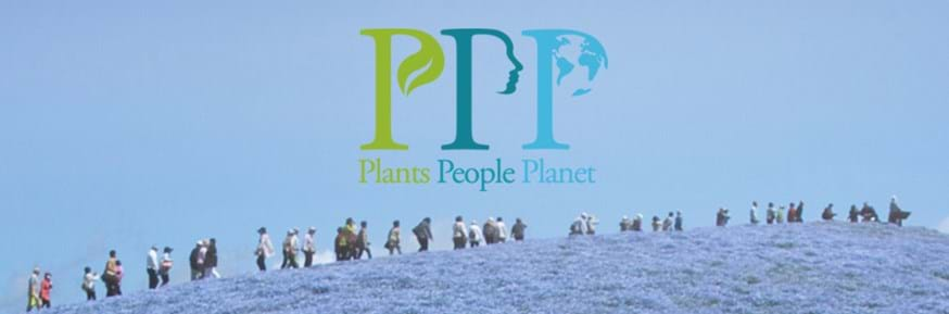 Plants, People, Planet logo over people walking through a meadow of blue flowers