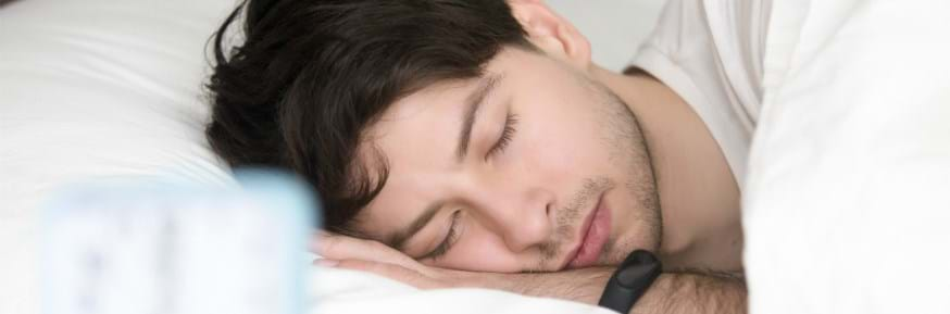 A man sleeping wearing a smart watch