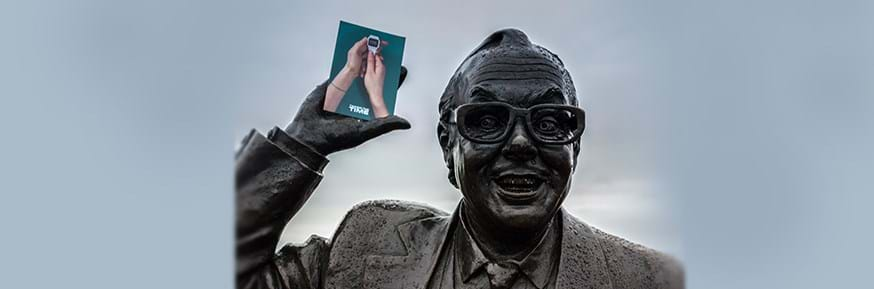 Eric Morecambe statue holding the project flyer showing a Casio watch in a pair of hands