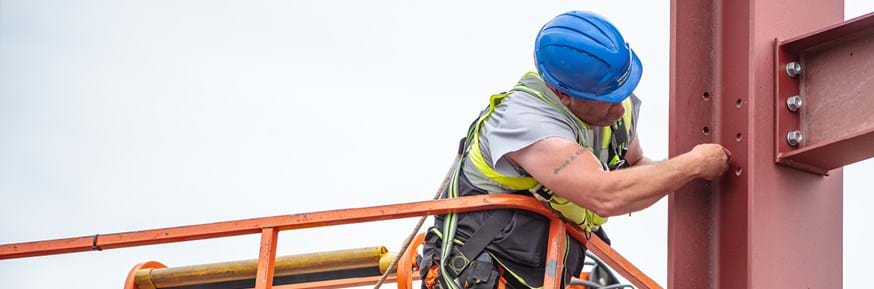 Picture of a construction worker at high level fixing some steelwork