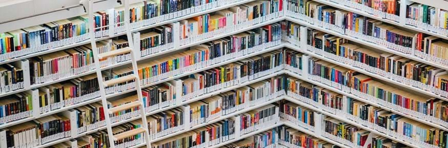 White bookshelves in a library, with rows of close-packed colourful spines of books.