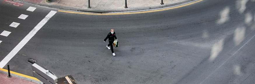 Man wearing a face mask crosses an empty street.