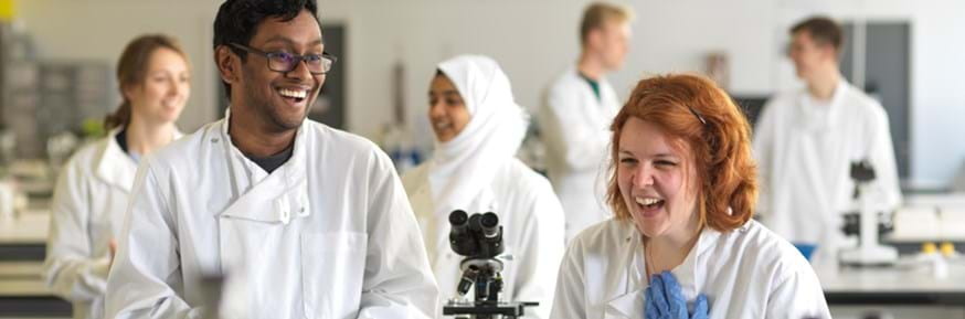 A diverse group of students laughing together in a teaching laboratory setting with microscopes, wearing white lab coats, blue lab gloves