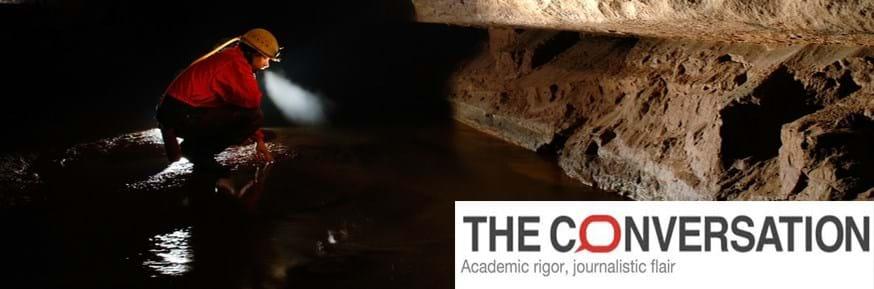 A person crawling through a dark cave