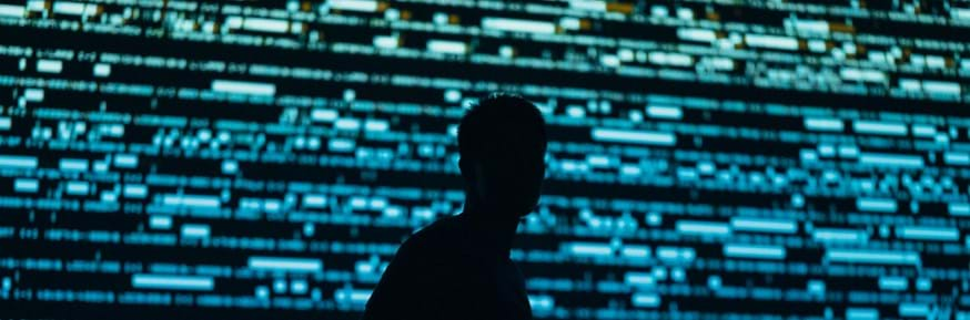 Silhouette of a person in front of a screen of code