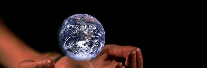 A pair of hands, cupped. A miniature representation of the planet Earth is floating above them.