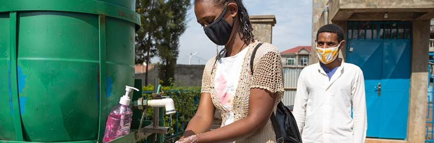 A young woman wearing a face covering and washing her hands at a cleaning station in Ethiopia