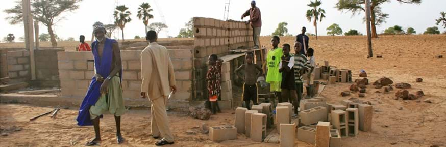 In a dry sandy landscape with scattered palm trees, a group of Malian villagers, including their Chief and some young boys, are in the early stages of building a hospital from concrete breeze-blocks.