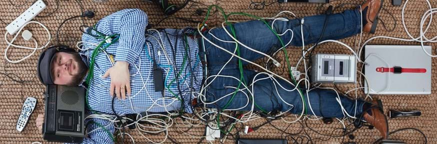 An image of a man led down entwined with cables and surrounded by electrical appliances