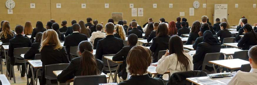 School pupils sitting an exam in a large hall