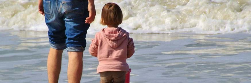 Little girl paddling in the sea with her father