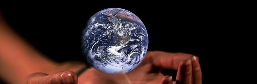 World globe hovering over hands