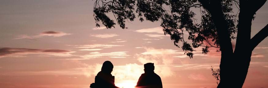 Silhouettes of two people sat on chairs against a sun set.