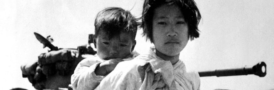 Korean woman and child in front of American tank,  1951