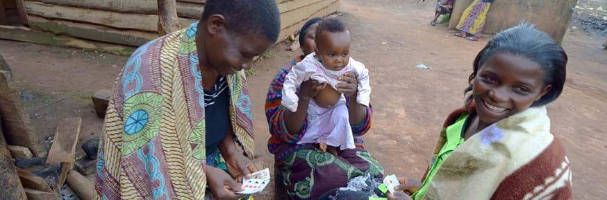 Young Malawian women playing cards - one young woman holding a baby