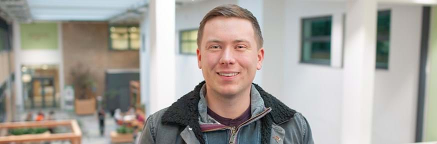 Prizewinning student Matt Jones  smiles to the camera inside Lancaster Environment Centre's social covered courtyard space