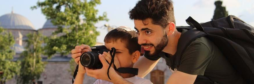 Mohammed Hajo, one of the Syrian refugees who participated in the project, with a Turkish child in Istanbul who approached him to teach him how to take photographs. This moment was captured by another Syrian refugee participant of the project.