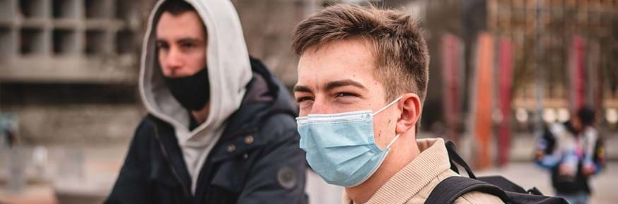 Two young men wearing masks during the COVID-19 pandemic.