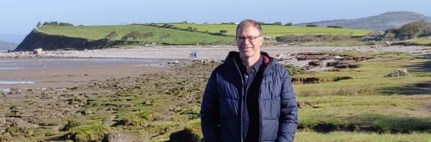 Nigel Watson standing on the shore of Morecambe Bay in the sunshine