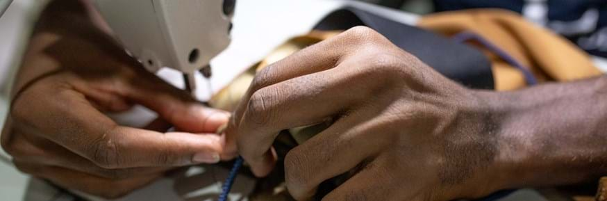 A close up image of a person using a sewing machine
