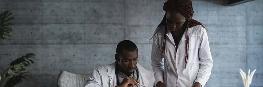 Two doctors, one male and one female, looking at information on a desktop