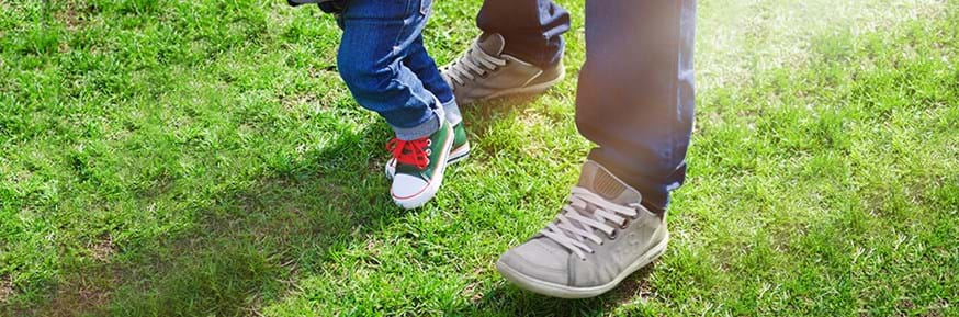 Child and Adult legs and feet together on the grass