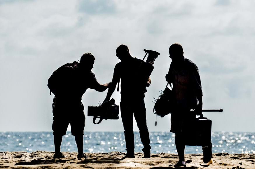 A film crew on a beach