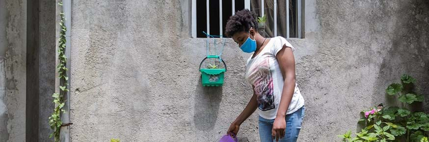 A young girl watering plants in Ethiopia while wearing a face mask to protect against Covid-19.