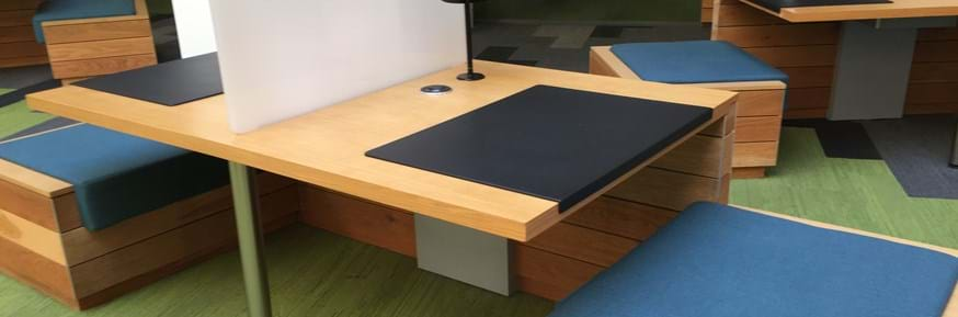 Library study space, wooden desk adjacent to the tree on A floor.