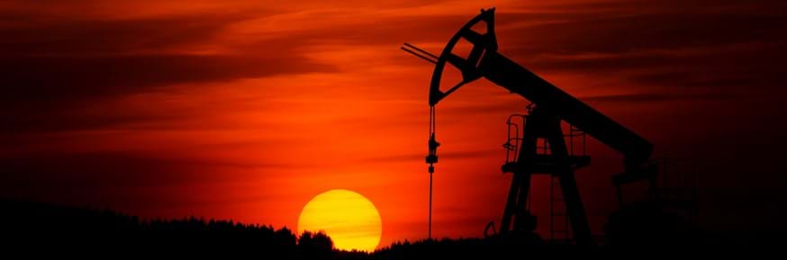 An oil well operating in the desert in front of the setting sun